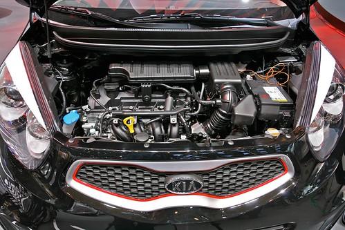 Открыт капот и виден двигатель автомобиля Kia